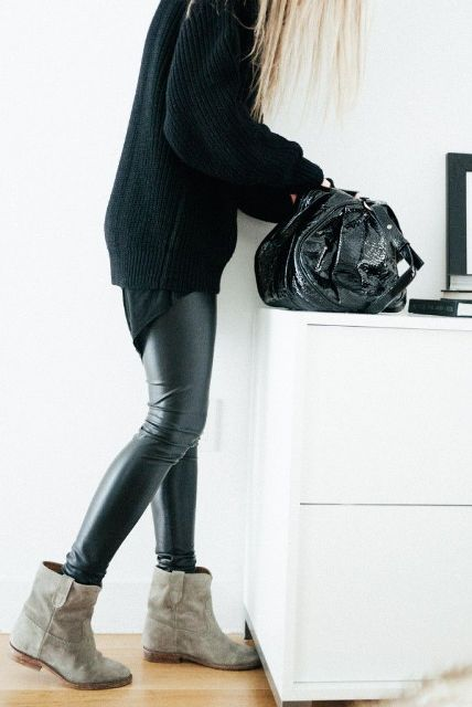 an oversized black sweater, black leather pants, grey booties and a lacquer black bag