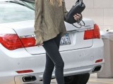 an oversized metallic top, black skinnies, black booties, a black clutch and a purple hat