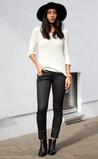a monochromatic look with blakc jeans, a white top, black ankle boots and a black hat