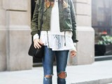 a white lace top, a white sweater, an olive green cropped jacket, blue ripped skinnies, ocher booties, a black hat and a black bag