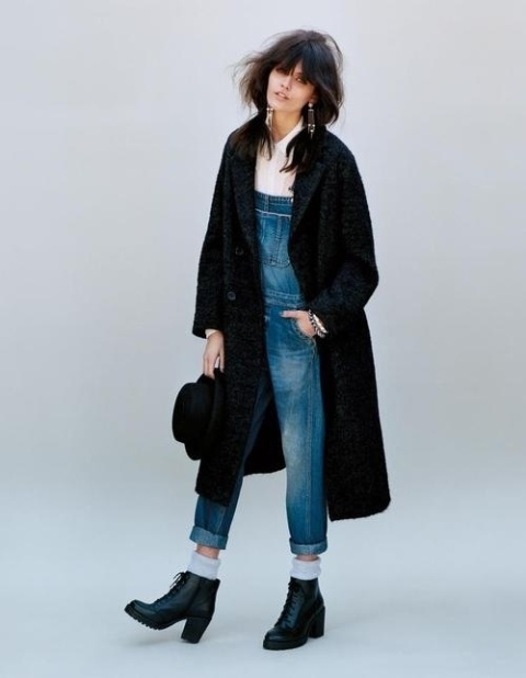 a blush shirt, a denim overall, black booties, a black coat and a black hat for a boho touch