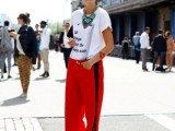 a trendy look with a printed tee, red side-striped pants, statement necklaces and a clutch bag