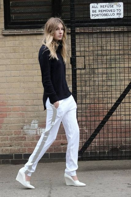 a casual look with a black turtleneck, white side striped pants, white wedges