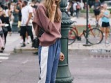 a casual sporty look with an oversized dusty pink sweatshirt, blue side-striped pants, matching trainers and a black bag