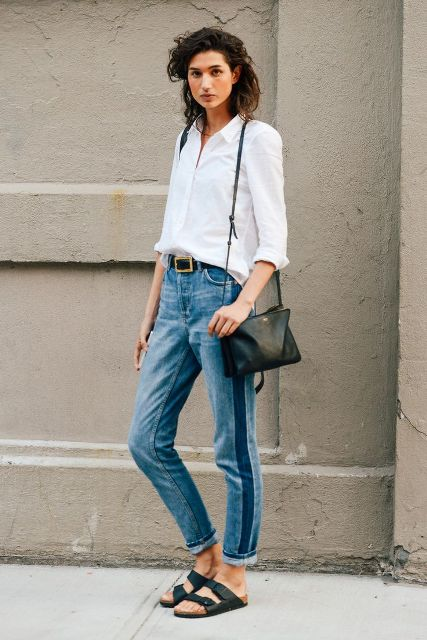 a white shirt, blue side-striped jeans, black birkenstocks and a black bag for a casual outfit