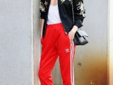 a bright outfit with a white top, red side-striped sport pants, red shoes, a black embroidered bomber and a black bag