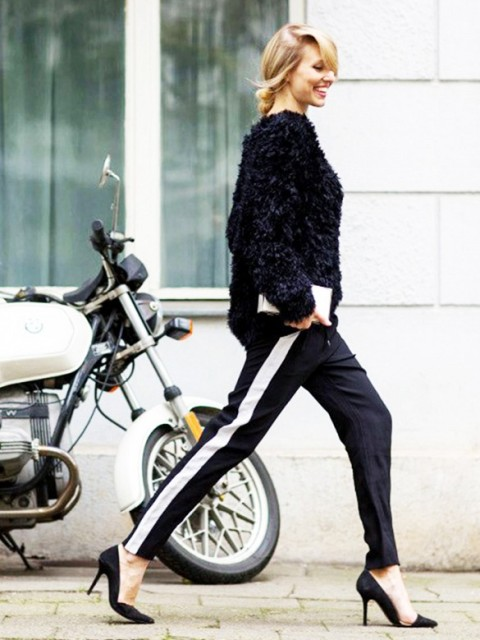 a chic outfit with black side-striped pants, black heels, a black faux fur coat for a statement