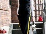 a white turtleneck, a black jumpsuit with yellow stripes on the sides, white shoes and a contrasting backpack
