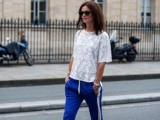 a bright look with a white lace top with short sleeves, bright blue pants with side stripes and heels