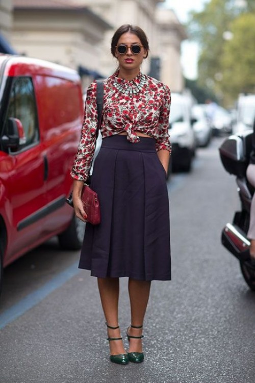a creative work look with a bright crop top with long sleeves, a deep purple pleated skirt, green shoes and a burgundy clutch