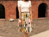 a chic work look with a white crop top, a midi floral A-line skirt, orange shoes and a clear clutch