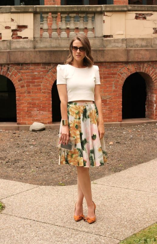 a chic work look with a white crop top, a midi floral A line skirt, orange shoes and a clear clutch