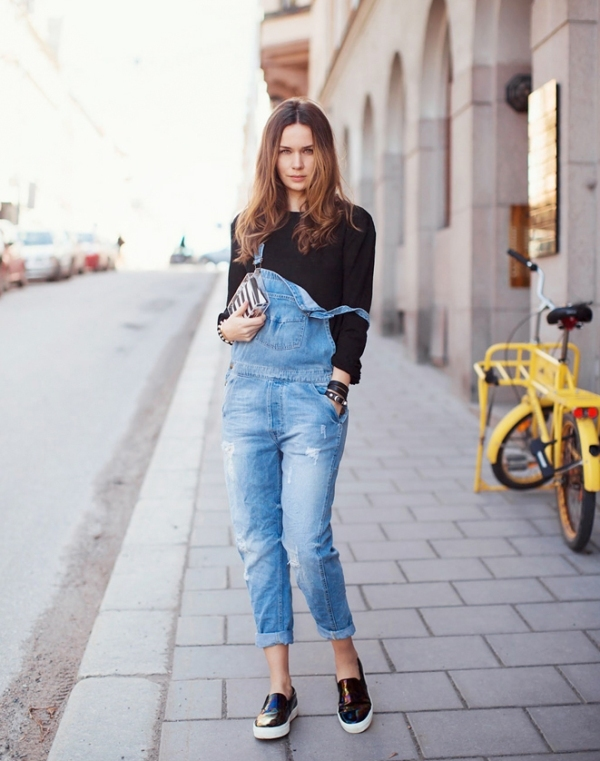 a black top, a blue denim dungaree and black slipons for a comfortable spring look