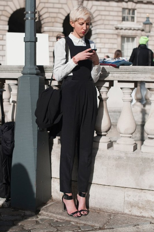 a monochromatic look with a white shirt, a black dungaree, black shoes and a black bag is a nice outfit for work