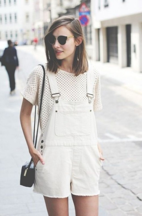 a white poerforated top, a whiet denim dungaree with shorts, a black crossbody for an effortless summer look