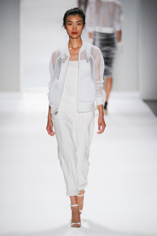 a black top, a white dungaree, white heels and a white net jacket to cover up a bit