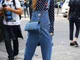 a navy and white polka dot top, a blue denim dungaree, a light blue bag and blue sneakers for spring