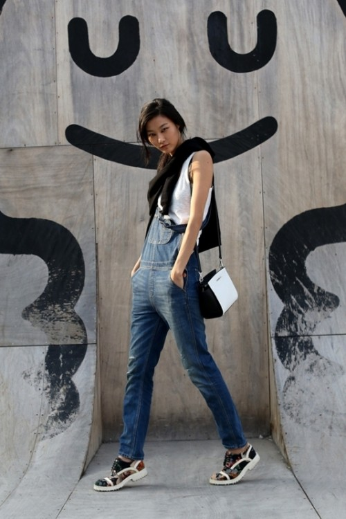 a white sleeveless top, a navy denim dungaree, a two-tone bag and floral sneakers for a sping to summer look