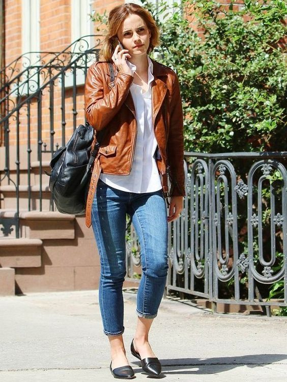 a white shirt,blue jeans, black flats, an amber leather jacket and a large black bag