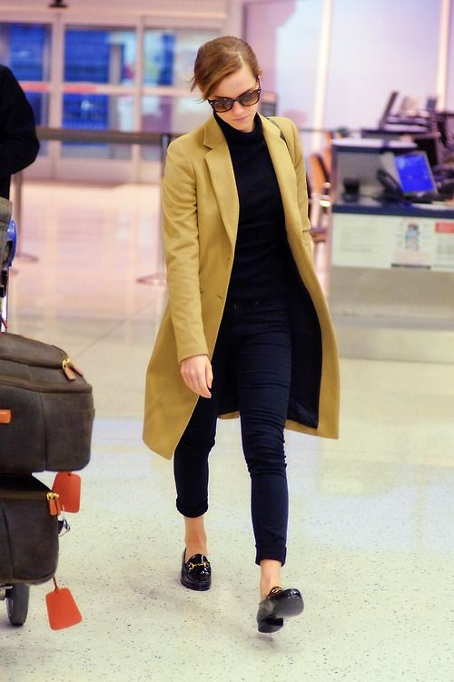 an elegant casual outfit with a black turtleneck, navy pants, black loafers and a mustard coat for a colorful accent