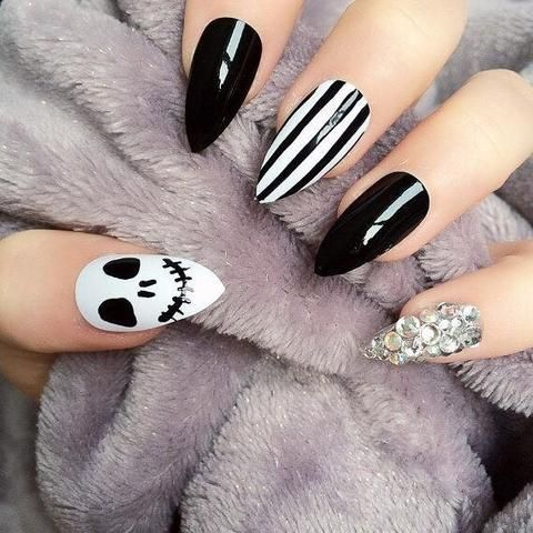 a black and white manicure with stripes, a skull and an embellished nail for Halloween