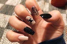 a creamy, clear and black glitter manicure with spiderwebs and spiders is a very refined solution for Halloween