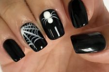 a glossy black manicure with a white spiderweb and a white spider is amazing for Halloween