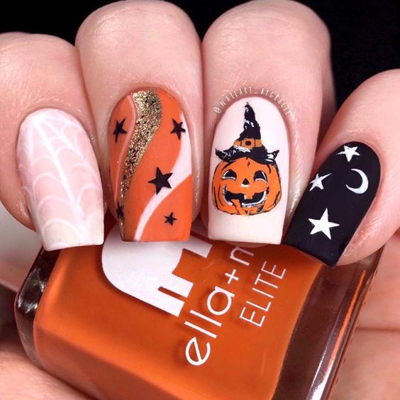 a nude, white, orange and black nail with a pumpkin, stars, moons and spiderwebs for Halloween