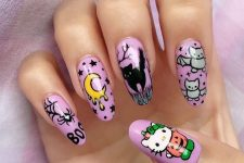 a purple manicure with black cats, spiders and spiderwebs, a moon, some bats and Hello Kitty