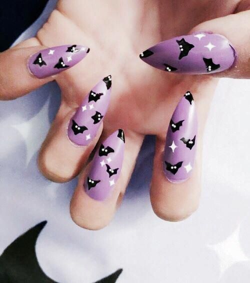 a purple manicure with white stars and small black bats for Halloween will add a bit of color