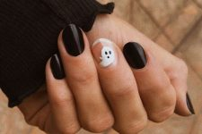 glossy black nails and a nude accent one with a ghost for Halloween, this is classics