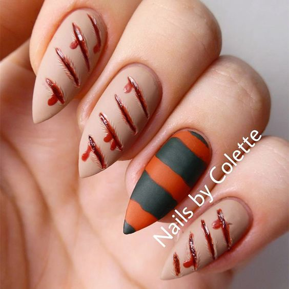 matte nude nails with bleeding scratches, a striped black and orange accent nail for Halloween