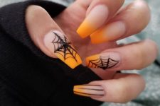 nude and orange nails with spiderwebs and rhinestones for a chic and bright Halloween look