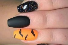 orange and black glitter nails with bats for a bold Halloween look that rocks