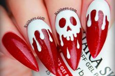 sharp red glitter nails with white marks and a skull in the center is a very bold and cool idea for Halloween