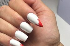 white nails with shapr ones with blood show off vampire teeth, which is a very bold and edgy solution