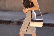a black sleeveless top, a neutral pencil skirt to accent the legs and not only, metallic shoes and a black and white bag