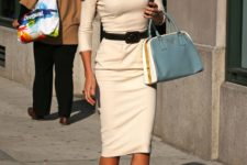 a creamy midi dress with long sleeves and a sexy cut, a belt on the waist to accent it, nude shoes and a blue bag