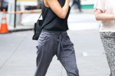 a halter neckline top, black strappy shoes and grey pants plus a black bag for a sexy summer work look