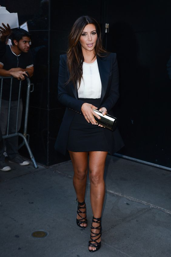 a white top, a black mini and black strappy shoes to accent the long legs, and a long black tux blazer