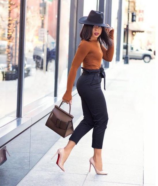black high waisted cropped pants, a rust-colored top with long sleeves, nude heels, a black hat and a taupe bag - everything is accented