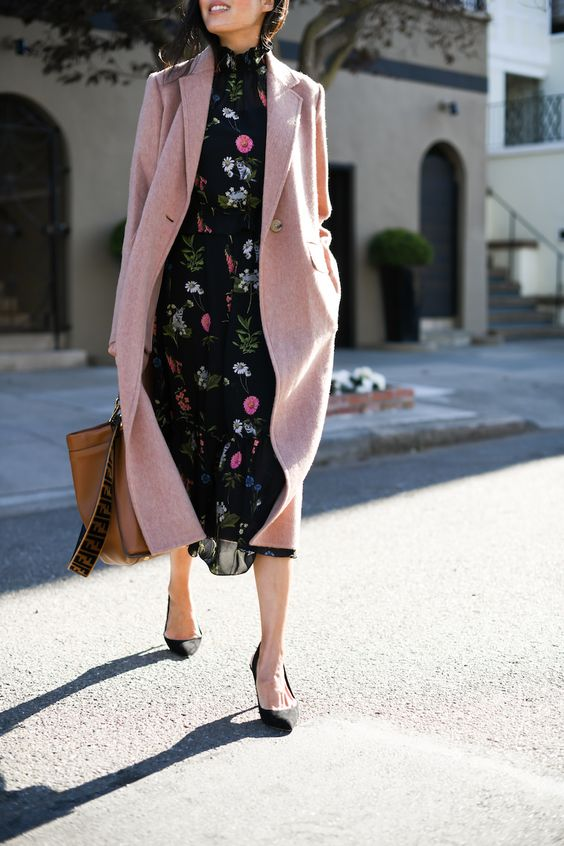 a black floral midi dress with a high neckline, black shoes, a pink coat and a brown tote for work