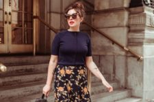 a fall work look with a black button up, a dark floral midi skirt, a black backpack and orange shoes