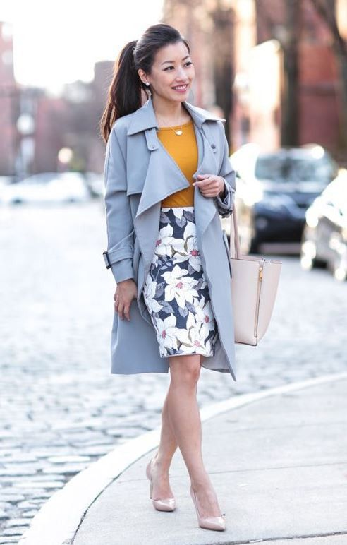 a spring work outfit with a mustard tee, a pastel floral knee skirt, a powder blue trench, blush shoes and a blush bag