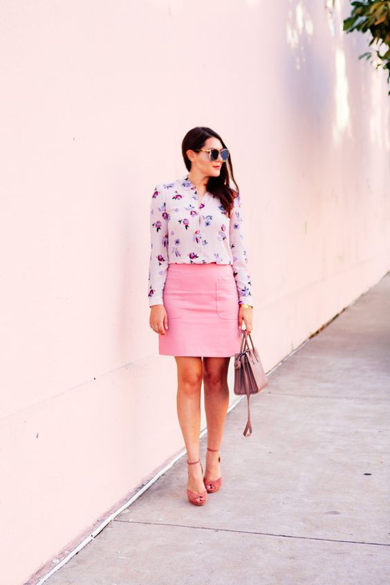 a summer work outfit with a bright floral shirt, a pink skirt, pink shoes and a mauve bag