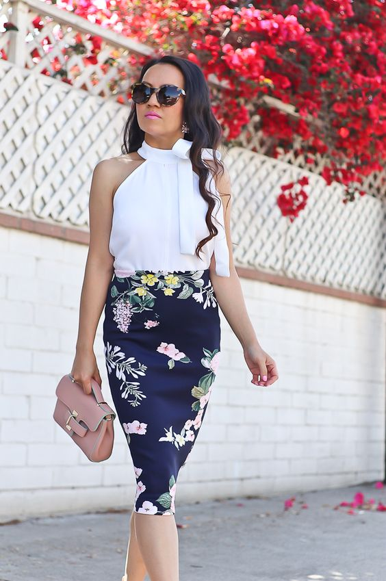 a summer work outfit with a white halter neckline bow top, a dark floral midi skirt, a pink bag