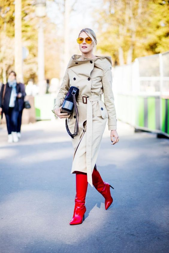 a neutral oversized trench with black buttons and a hood is balanced with red boots that add color