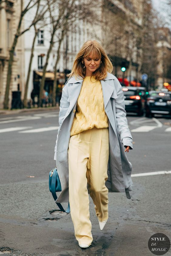 a powder blue midi trench paired wiht a sunny yellow look and a turquoise bag for a springy feel