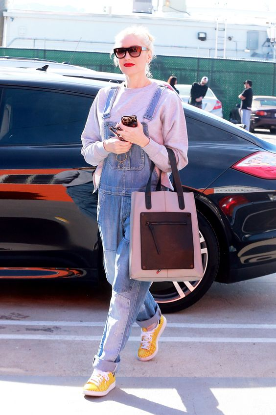 Gwen Stefani wearing a grey sweatshirt, a blue denim overall and yellow shoes plus a large tote