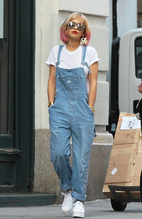 Rita Ora wearing a white tee, a blue denim dungaree, white sneakers and statement earrings just wows